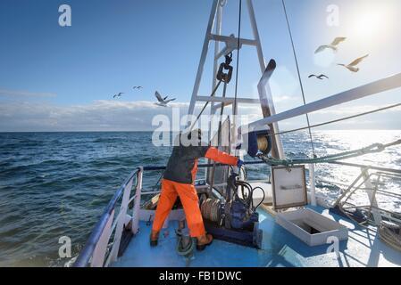Fisherman standing on deck of trawler - Stock Photo