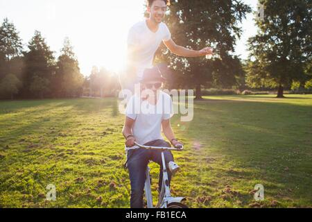 Party going man arriving in park standing on back of bicycle at sunset - Stock Photo