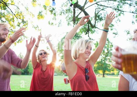 Adult friends dancing at sunset party in park - Stock Photo
