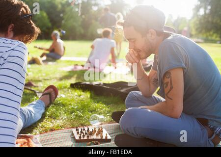 Young adults playing board game at sunset party in park - Stock Photo