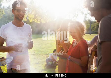 Adults friends eating and drinking at sunset party in park - Stock Photo