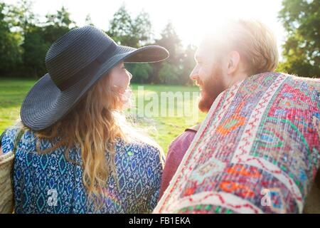 Rear view of romantic young couple carrying rug for picnic in park - Stock Photo