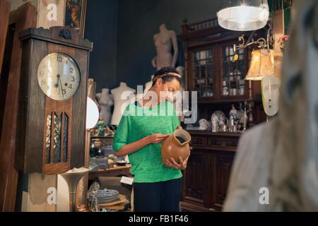Young woman looking at jug price ticket in vintage shop - Stock Photo