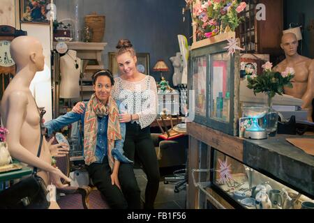 Portrait of two female colleagues in vintage shop - Stock Photo