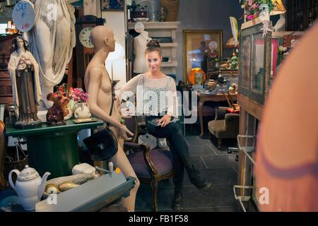 Portrait of stylish young woman sitting in vintage shop - Stock Photo