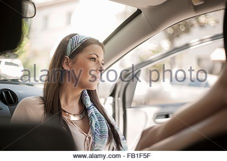 Young woman, sitting, relaxing in car - Stock Photo