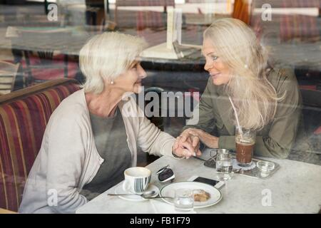 Mother and daughter sitting together in cafe, holding hands, seen through cafe window - Stock Photo