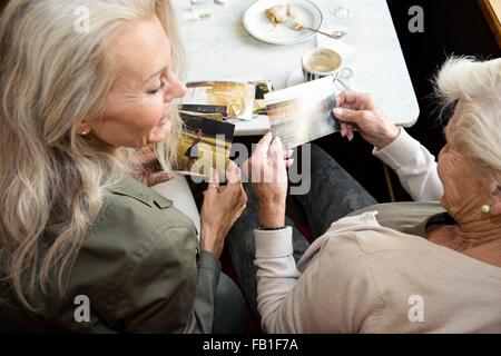 Mother and daughter sitting together in cafe, looking at photographs, rear view - Stock Photo