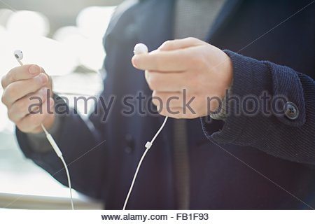 Young man holding earphones, outdoors, mid section - Stock Photo