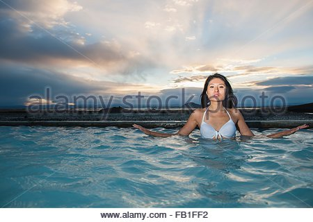 Woman enjoying the warm water, in geothermal bath, North Iceland - Stock Photo