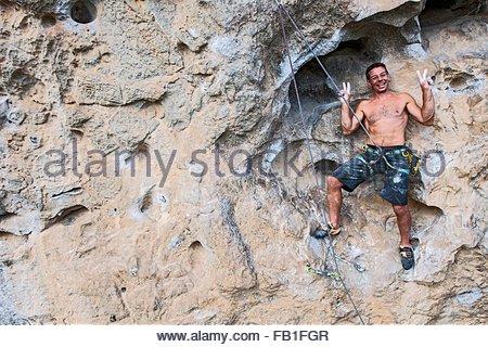 Rock climber rock face White mountain peace sign smiling Yangshuo Guangxi Zhuang China - Stock Photo