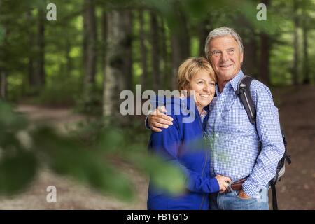 Portrait of couple standing in forest - Stock Photo