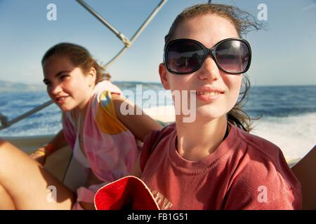Two teenage girls on boat at sea - Stock Photo