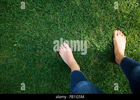 Woman standing on grass, low section, elevated view - Stock Photo
