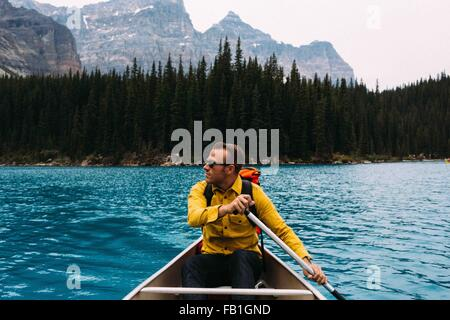 Front view of mid adult man paddling canoe, looking away, Moraine lake, Banff National Park, Alberta Canada - Stock Photo