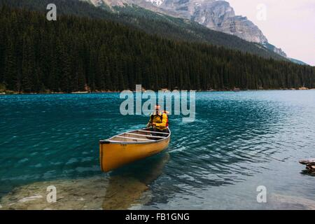 Mid adult man paddling canoe on Moraine lake, looking at camera, Banff National Park, Alberta Canada - Stock Photo