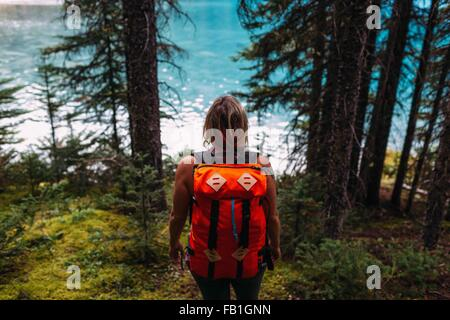 rear view mid adult woman carrying orange colour backpack forest water Moraine lake Banff National Park Alberta - Stock Photo