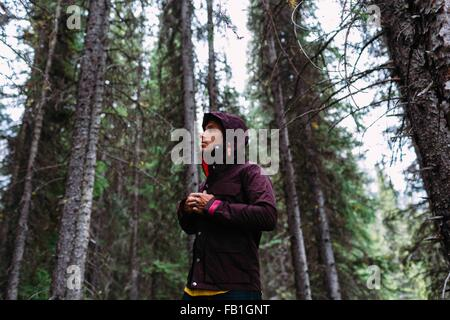Low angle view mid adult man forest fastening waterproof coat away Moraine lake Banff National Park Alberta Canada - Stock Photo