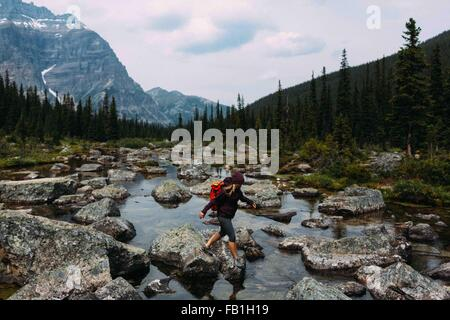 Side view of mid adult woman walking on rocky riverbed, Moraine lake, Banff National Park, Alberta Canada - Stock Photo