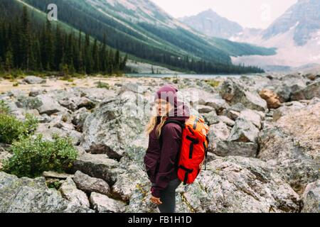 Side view mid adult woman rocky landscape carrying backpack camera smiling Moraine Lake Banff National Park Alberta - Stock Photo