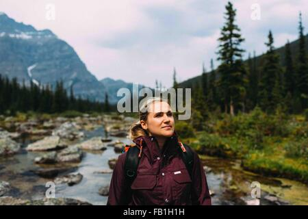Mid adult woman hiking on Moraine Lake, looking away, Banff National Park, Alberta Canada - Stock Photo