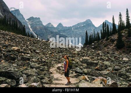 Side view of mid adult woman on rocky landscape beneath mountain range, Moraine lake, Banff National Park, Alberta - Stock Photo