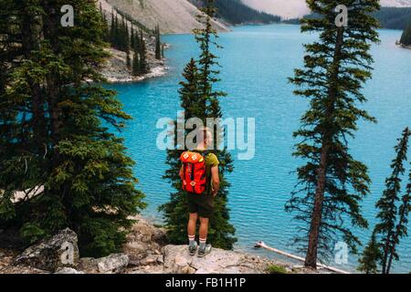 Rear view of mid adult man standing on cliff edge looking at elevated view of Moraine lake, Banff National Park, - Stock Photo