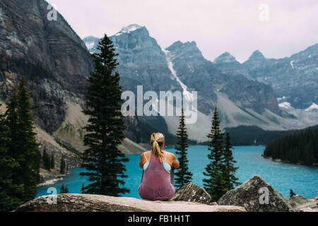 Rear view of mid adult woman on cliff edge looking at elevated view of Moraine lake, Banff National Park, Alberta - Stock Photo