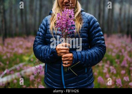 Cropped view of mid adult woman wearing padded coat holding wildflowers, Moraine lake, Banff National Park, Alberta Canada