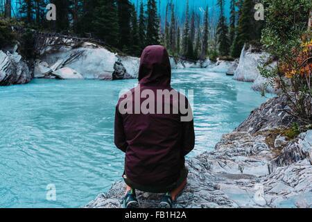 Rear view mid adult man wearing hooded waterproof coat crouching waters edge Moraine lake Banff National Park Alberta - Stock Photo