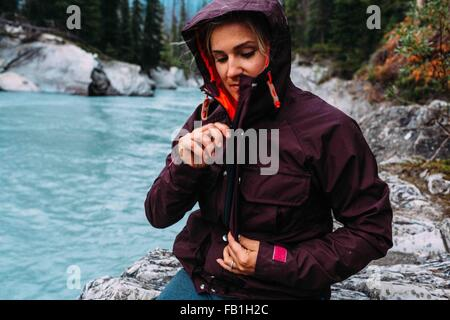 Mid adult woman by waters edge zipping up waterproof coat, Moraine lake, Banff National Park, Alberta Canada - Stock Photo