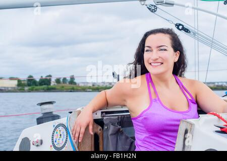 Young woman wearing vest on sailboat looking away smiling - Stock Photo