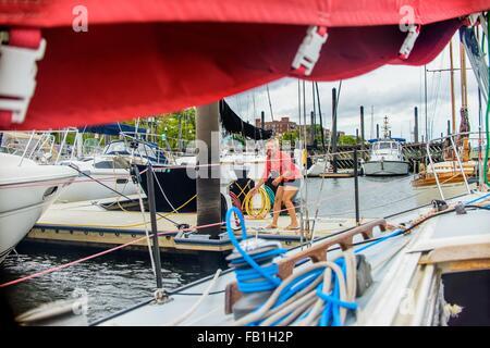 Young woman on marina pier mooring sailboat looking at camera smiling - Stock Photo