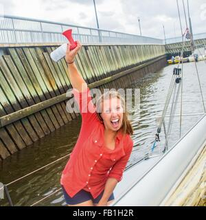 Young woman on sailboat in marina arm raised holding air horn, looking at camera open mouthed smiling - Stock Photo