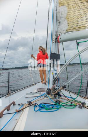 Full length rear view of young woman on bow of sailboat looking away - Stock Photo
