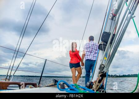 Rear view of couple on bow of boat holding hands, looking over shoulder at camera smiling - Stock Photo