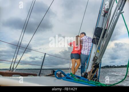 Rear view of couple on bow of boat kissing - Stock Photo