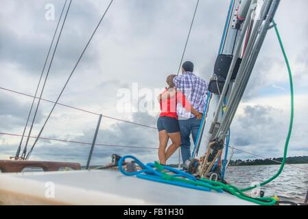 Rear view of couple on bow of arms around each other - Stock Photo