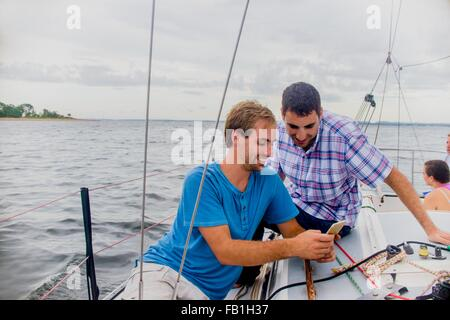 Men on sailboat looking at mobile phone smiling