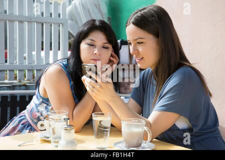 Young woman with mother and baby daughter reading smartphone text in cafe - Stock Photo
