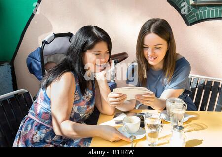 Young woman with mother and baby daughter looking at photographs at sidewalk cafe - Stock Photo
