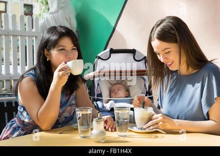 Young woman with mother and baby daughter drinking coffee at sidewalk cafe - Stock Photo