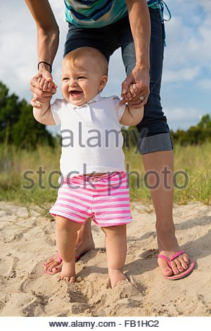 Mid adult woman holding baby daughters hands while toddling in sand - Stock Photo