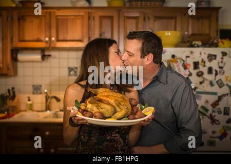 Mature couple kissing whilst holding roast chicken dinner in kitchen - Stock Photo