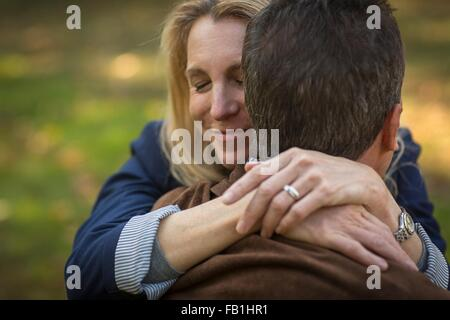 Close up of romantic mature couple hugging in garden - Stock Photo