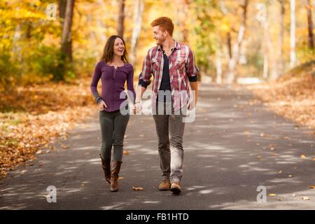 Romantic young couple strolling in autumn forest - Stock Photo