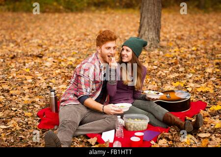 Young couple having picnic in autumn forest - Stock Photo
