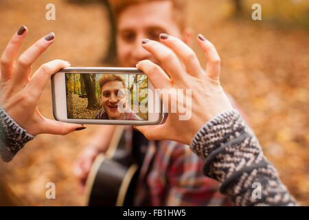 Hands of young woman photographing boyfriend on smartphone in autumn forest - Stock Photo