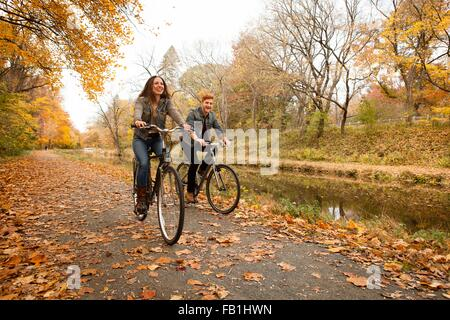Happy young couple cycling along riverside in autumn - Stock Photo