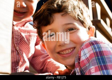 Close up of boy with big brother looking at camera smiling - Stock Photo